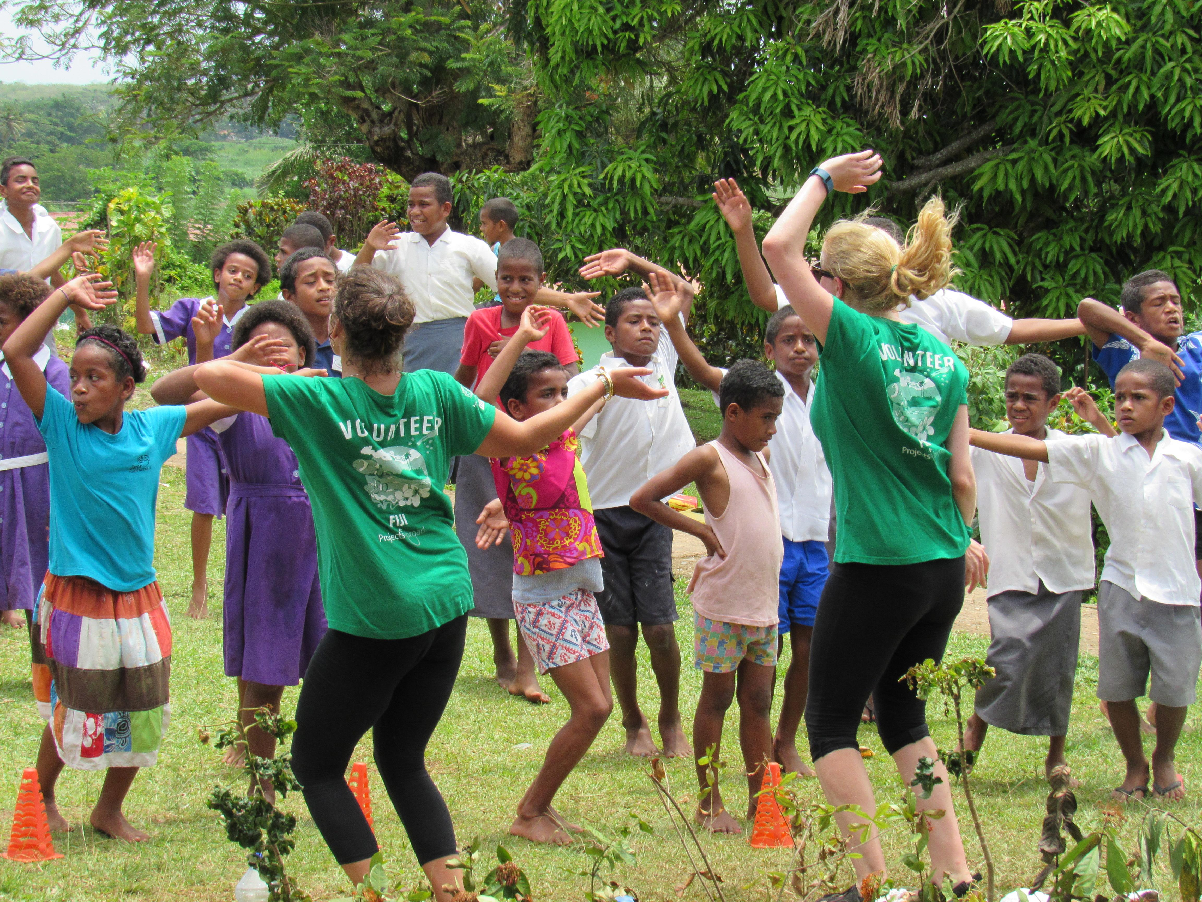 Two interns from Projects Abroad pictured teaching Zumba to a school class as part of their nutrition internship in Fiji.